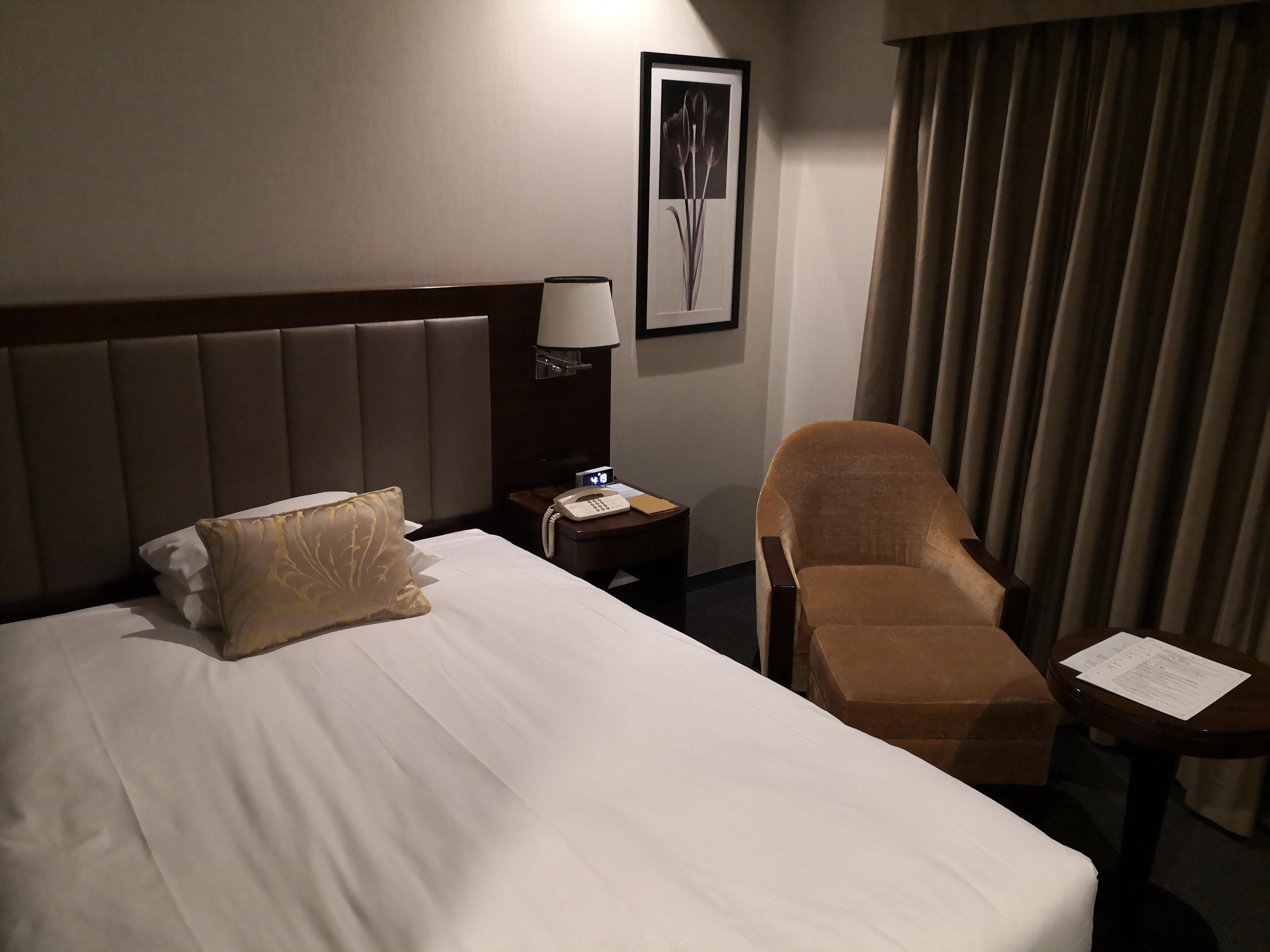 ベッド脇の様子。ナイトスタンドと一人掛けソファー、丸テーブルがある